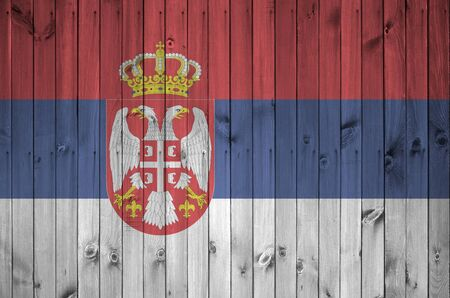 Serbia flag depicted in bright paint colors on old wooden wall close up. Textured banner on rough background