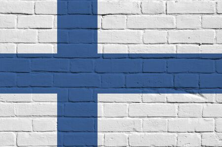 Finland flag depicted in paint colors on old brick wall close up. Textured banner on big brick wall masonry background Фото со стока
