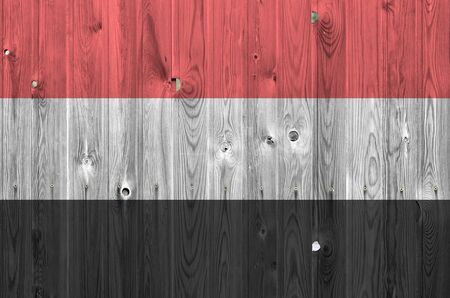 Yemen flag depicted in bright paint colors on old wooden wall close up. Textured banner on rough background