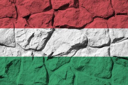 Hungary flag depicted in paint colors on old stone wall close up. Textured banner on rock wall background Фото со стока