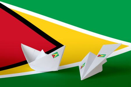 Guyana flag depicted on paper origami airplane and boat. Oriental handmade arts concept Stock fotó