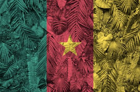 Cameroon flag depicted on many leafs of monstera palm trees. Trendy fashionable background