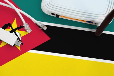 Mozambique flag depicted on table with internet rj45 cable, wireless usb wifi adapter and router. Internet connection concept