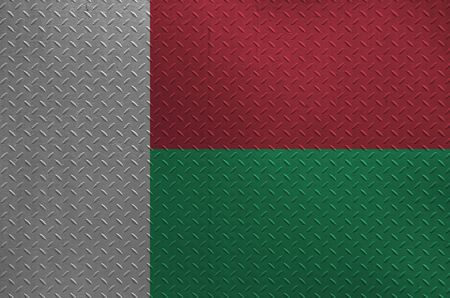 Madagascar flag depicted in paint colors on old brushed metal plate or wall close up. Textured banner on rough background