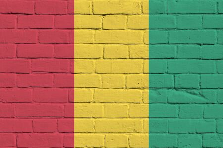Guinea flag depicted in paint colors on old brick wall close up. Textured banner on big brick wall masonry background Stock fotó