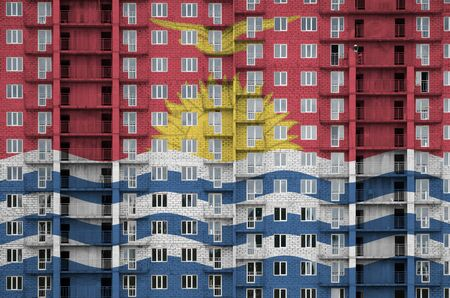 Kiribati flag depicted in paint colors on multi-storey residental building under construction. Textured banner on big brick wall background