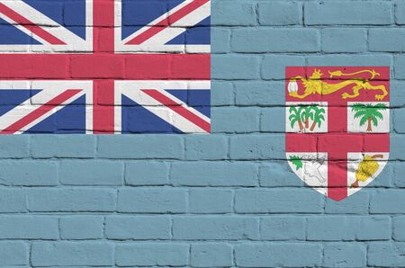 Fiji flag depicted in paint colors on old brick wall close up. Textured banner on big brick wall masonry background