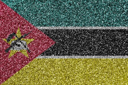 Mozambique flag depicted on many small shiny sequins. Colorful festival background for disco party
