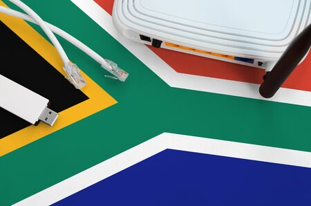 South Africa flag depicted on table with internet rj45 cable, wireless usb wifi adapter and router. Internet connection concept