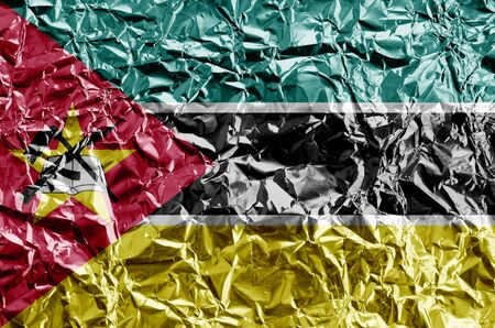 Mozambique flag depicted in paint colors on shiny crumpled aluminium foil close up. Textured banner on rough background