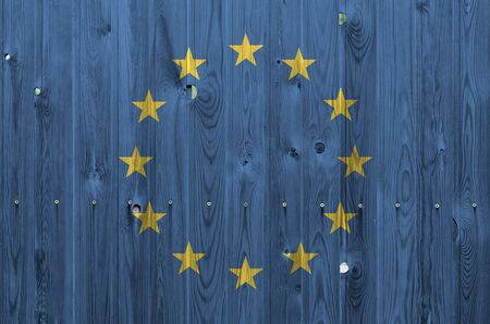 European union flag depicted in bright paint colors on old wooden wall close up. Textured banner on rough background