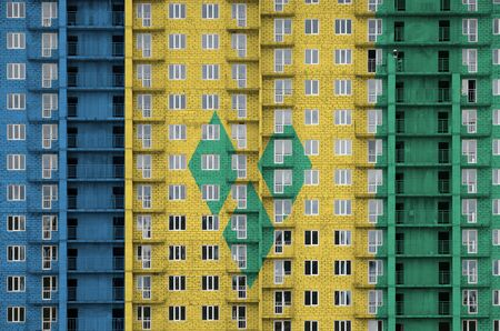 Saint Vincent and the Grenadines flag depicted in paint colors on multi-storey residental building under construction. Textured banner on big brick wall background