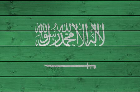 Saudi Arabia flag depicted in bright paint colors on old wooden wall close up. Textured banner on rough background