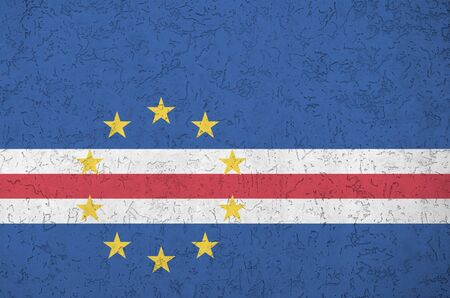 Cabo verde flag depicted in bright paint colors on old relief plastering wall close up. Textured banner on rough background