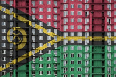 Vanuatu flag depicted in paint colors on multi-storey residental building under construction. Textured banner on big brick wall background