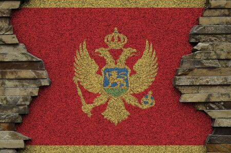 Montenegro flag depicted in paint colors on old stone wall close up. Textured banner on rock wall background Stockfoto