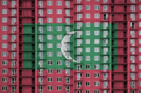 Maldives flag depicted in paint colors on multi-storey residental building under construction. Textured banner on big brick wall background Zdjęcie Seryjne