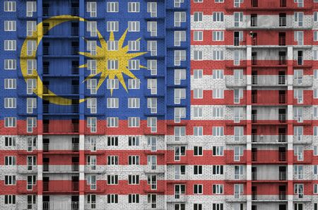 Malaysia flag depicted in paint colors on multi-storey residental building under construction. Textured banner on big brick wall background