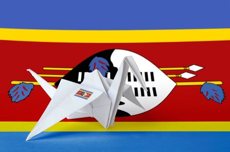Swaziland flag depicted on paper origami crane wing. Oriental handmade arts concept