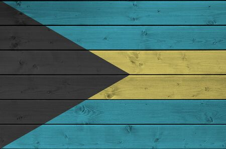 Bahamas flag depicted in bright paint colors on old wooden wall close up. Textured banner on rough background