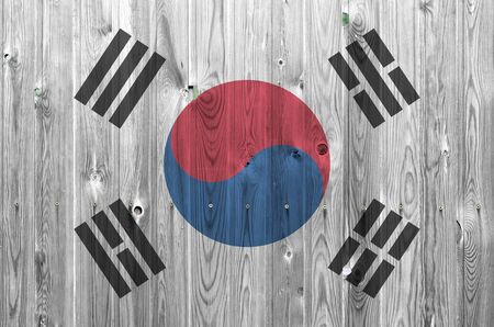 South Korea flag depicted in bright paint colors on old wooden wall close up. Textured banner on rough background