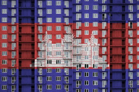 Cambodia flag depicted in paint colors on multi-storey residental building under construction. Textured banner on big brick wall background