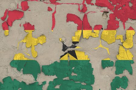Ghana flag depicted in paint colors on old obsolete messy concrete wall close up. Textured banner on rough background