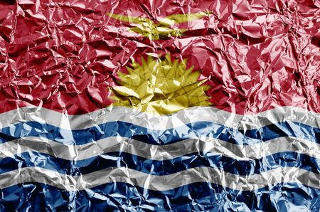 Kiribati flag depicted in paint colors on shiny crumpled aluminium foil close up. Textured banner on rough background Stock fotó