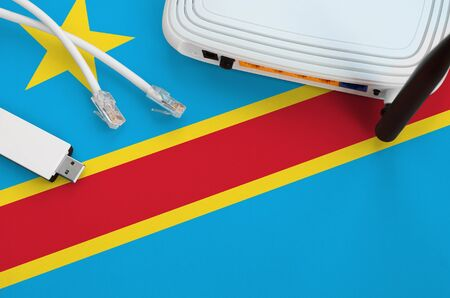 Democratic Republic of the Congo flag depicted on table with internet rj45 cable, wireless usb wifi adapter and router. Internet connection concept
