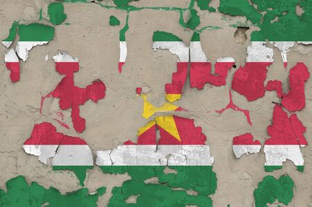Suriname flag depicted in paint colors on old obsolete messy concrete wall close up. Textured banner on rough background