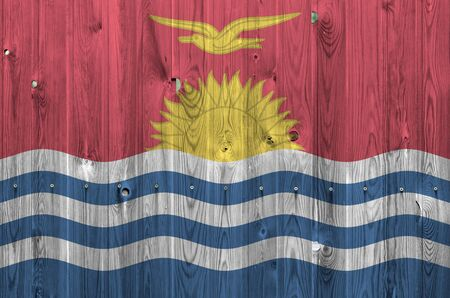Kiribati flag depicted in bright paint colors on old wooden wall close up. Textured banner on rough background