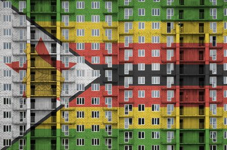 Zimbabwe flag depicted in paint colors on multi-storey residental building under construction. Textured banner on big brick wall background Zdjęcie Seryjne - 135358797