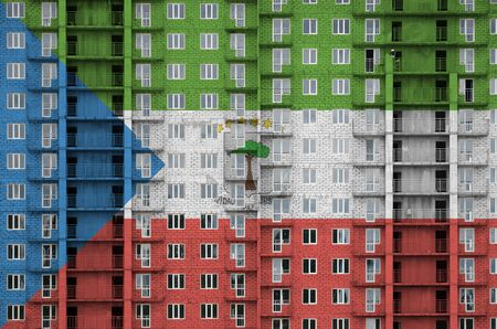 Equatorial Guinea flag depicted in paint colors on multi-storey residental building under construction. Textured banner on big brick wall background
