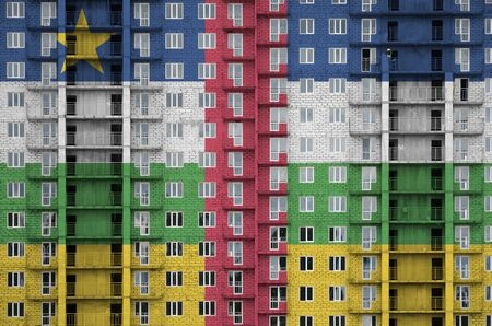 Central African Republic flag depicted in paint colors on multi-storey residental building under construction. Textured banner on big brick wall background