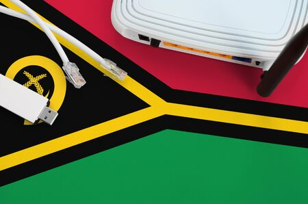 Vanuatu flag depicted on table with internet rj45 cable, wireless usb wifi adapter and router. Internet connection concept