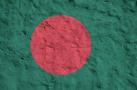 Bangladesh flag depicted in bright paint colors on old relief plastering wall close up. Textured banner on rough background