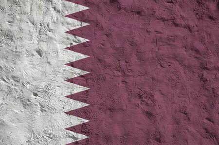 Katar-Flagge in leuchtenden Farben auf der alten Reliefputzwand hautnah dargestellt. Strukturiertes Banner auf rauem Hintergrund