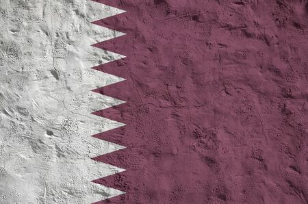 Qatar flag depicted in bright paint colors on old relief plastering wall close up. Textured banner on rough background