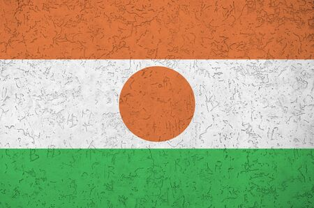 Niger flag depicted in bright paint colors on old relief plastering wall close up. Textured banner on rough background Stock Photo