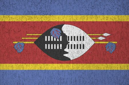 Swaziland flag depicted in bright paint colors on old relief plastering wall close up. Textured banner on rough background