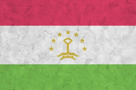 Tajikistan flag depicted in bright paint colors on old relief plastering wall close up. Textured banner on rough background