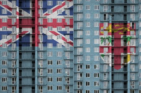 Fiji flag depicted in paint colors on multi-storey residental building under construction. Textured banner on big brick wall background Stock fotó