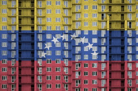 Venezuela flag depicted in paint colors on multi-storey residental building under construction. Textured banner on big brick wall background