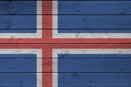 Iceland flag depicted in bright paint colors on old wooden wall close up. Textured banner on rough background