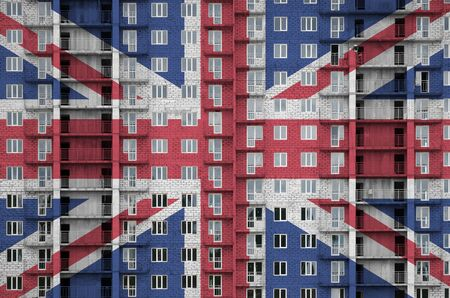 Great britain flag depicted in paint colors on multi-storey residental building under construction. Textured banner on big brick wall background