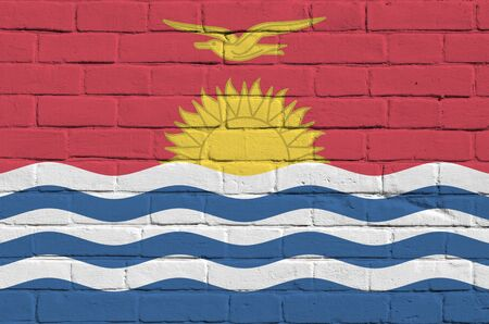 Kiribati flag depicted in paint colors on old brick wall close up. Textured banner on big brick wall masonry background