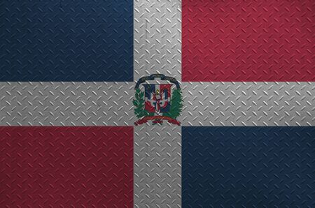 Dominican Republic flag depicted in paint colors on old brushed metal plate or wall close up. Textured banner on rough background