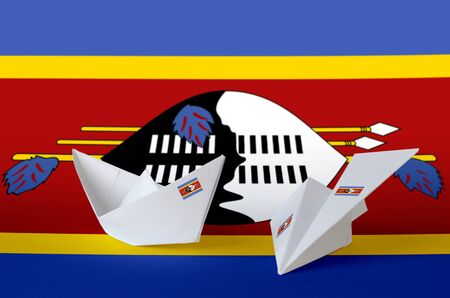 Swaziland flag depicted on paper origami airplane and boat. Oriental handmade arts concept Stock fotó