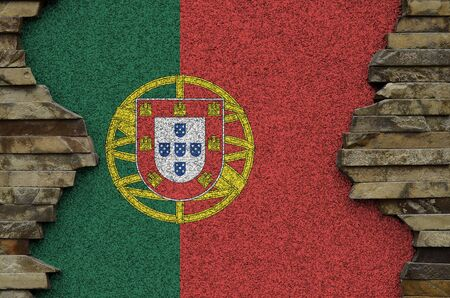 Portugal flag depicted in paint colors on old stone wall close up. Textured banner on rock wall background