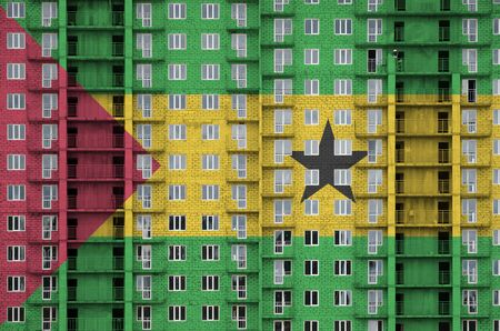 Sao Tome and Principe flag depicted in paint colors on multi-storey residental building under construction. Textured banner on big brick wall background